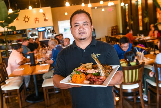 Peter Duenas, Global Master Chef corporate executive chef, displays a fiesta platter prepared at the Meskla Bistro - CHamoru Fusion restaurant in Tumon on Tuesday, May 7, 2019. The platter consists of portions of barbeque chicken, smoked pork, fried reef fish, keleguan, salad, red rice and titiyas.