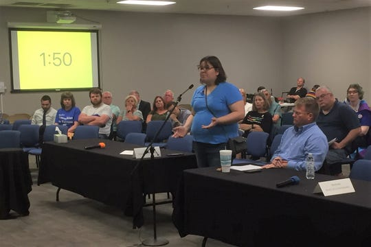 Natalie Skipworth, a transgender woman, speaks at a town hall meeting Monday evening on a proposed Fairness Ordinance as her allotted time counts down on the screen beside  her.
