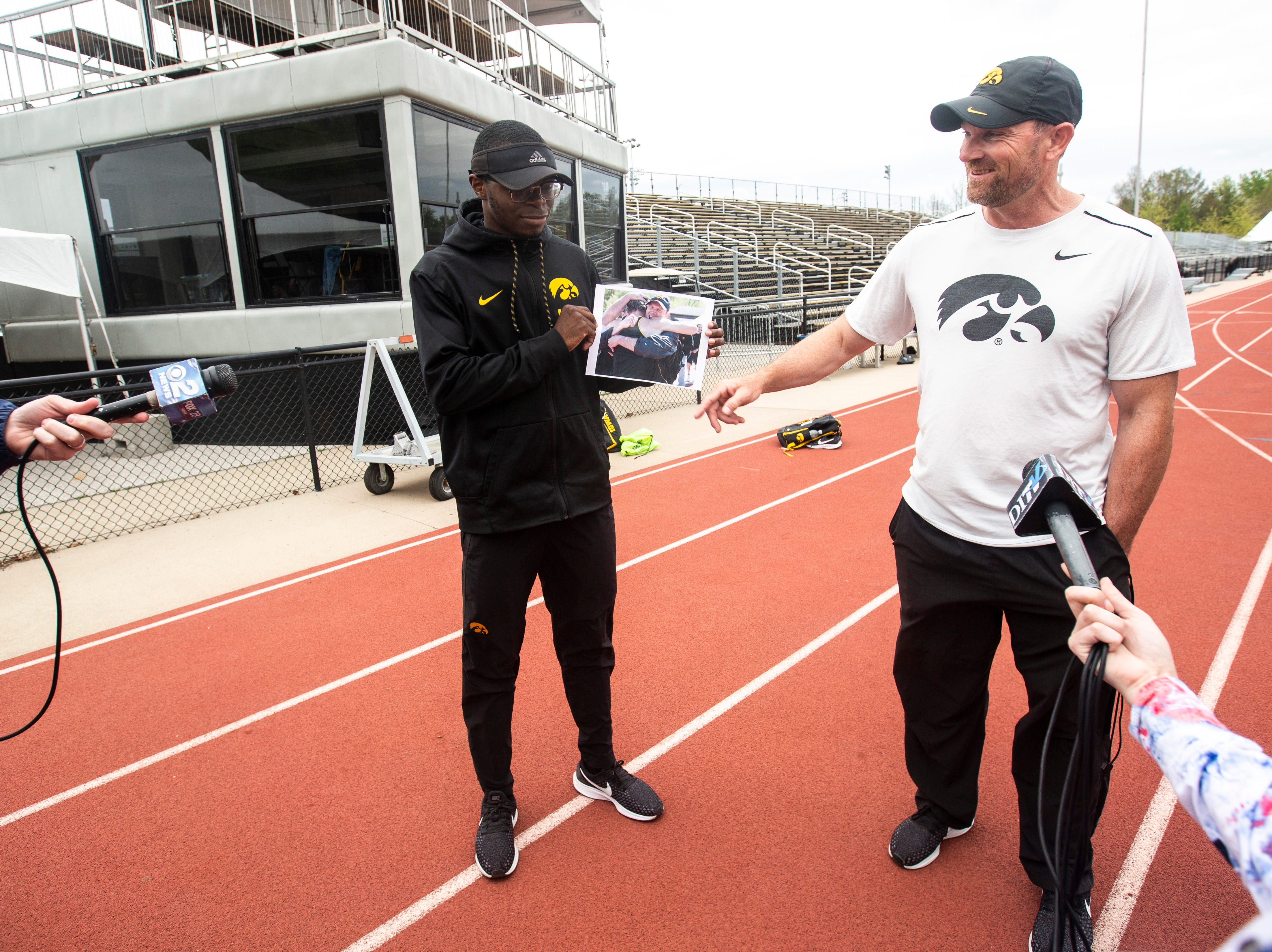 Iowa junior Jaylan McConico, left, holds up a photo of Joey Woody, the University of Iowa director of track and field, from 2011 while speaking with reporters, Tuesday, May 7, 2019, Francis X. Cretzmeyer Track in Iowa City, Iowa.