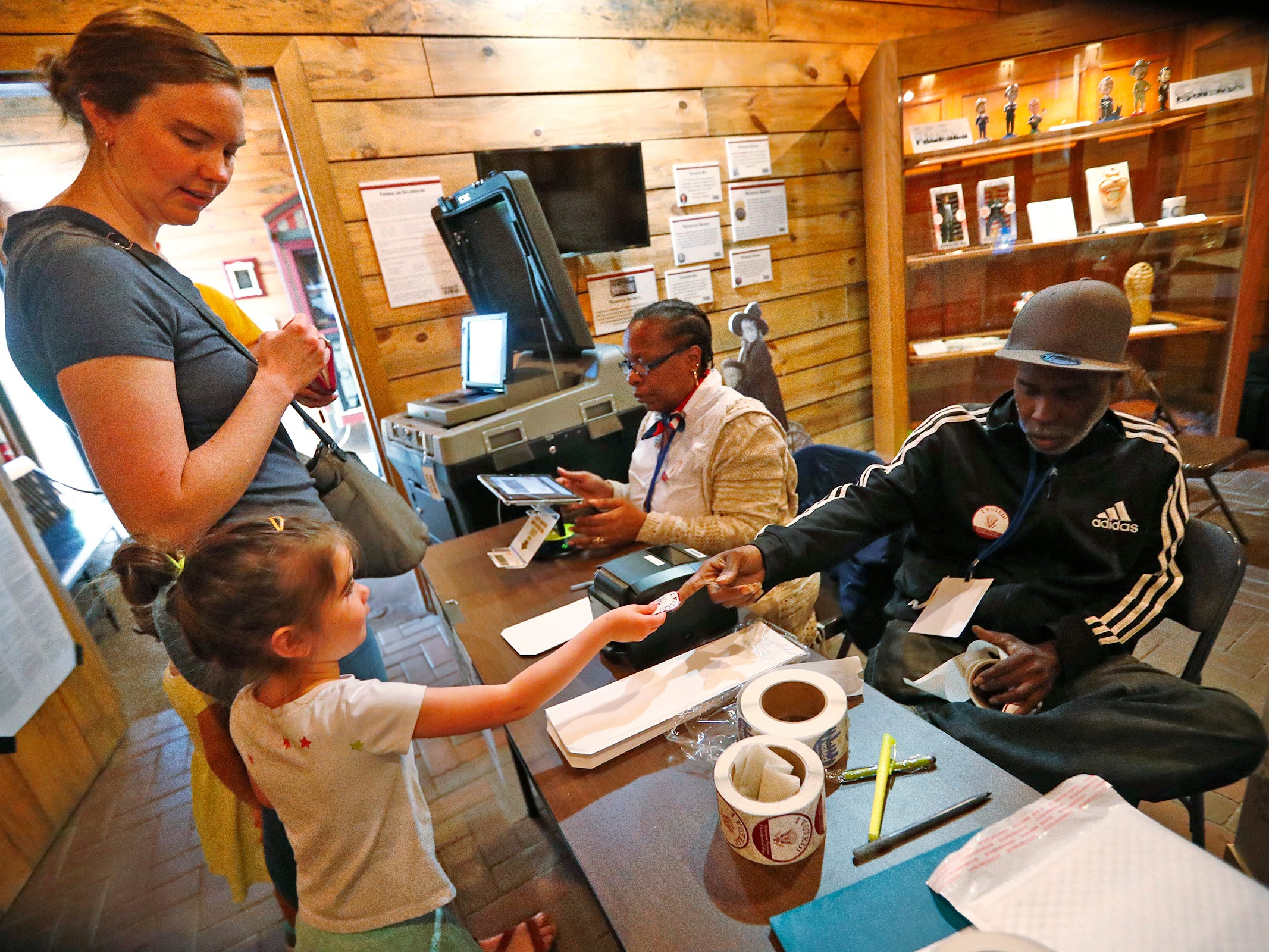 Esther Bulow signs in to vote as her daughter Opal Bulow gets a sticker from Election Clerk Aaron Howard, right, at the President Benjamin Harrison Presidential Site voting center, Tuesday, May 7, 2019.