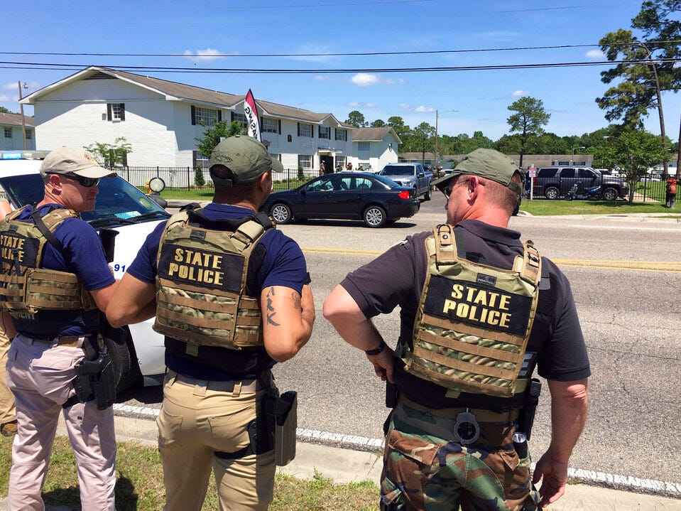 In this image provided by WLOX, Mississippi Bureau of Investigation officers watch as other officers converge on an apartment on Popp's Ferry Road in Biloxi, Miss., Monday, May, 6, 2019. Police were responding to a tip that Darian Taiwan Atkinson, 19, was at the apartment. Atkinson is accused of shooting Biloxi Police officer Robert McKeithen in an ambush in front of the police station Sunday night. He was not found in the apartment.