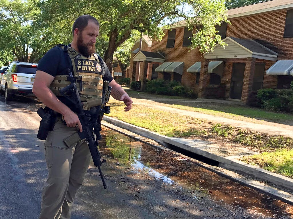 In this image provided by WLOX, a Mississippi Bureau of Investigation officer walks along Benachi Avenue in Biloxi, Miss., on Monday, May, 6, 2019, as he and other lawmen search for Darian Taiwan Atkinson, 19, who is accused of shooting Biloxi Police officer Robert McKeithen in an ambush in front of the police station Sunday night.