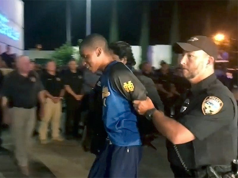 In this Monday, May 6, 2019 image taken from video, shooting suspect Darian Tawan Atkinson is lead into a police station in Biloxi, Miss. Police on Mississippi's Gulf Coast captured Atkinson, a suspect in the slaying of a uniformed officer gunned down outside a Biloxi police station, concluding a tense manhunt.