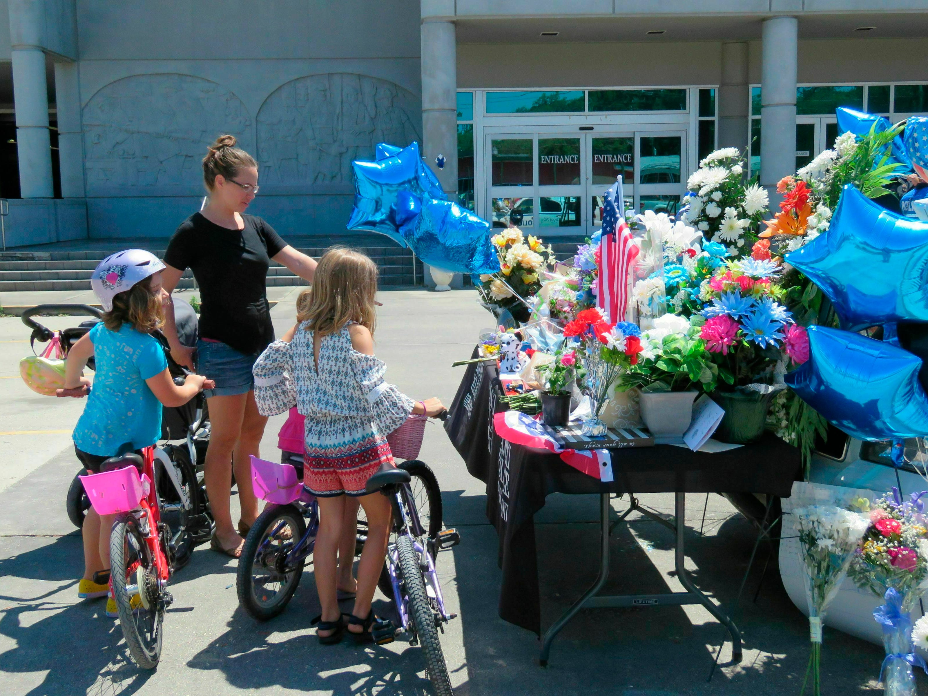 Natalie Rickert of Biloxi, Miss., and her daughters Alethea, 9, right,, London, 7, left, and Haven 5, hidden, look at a Biloxi police vehicle that was assigned to patrolman Robert McKeithen that is covered in flowers, Tuesday, May 7, 2019, in Biloxi, Miss.