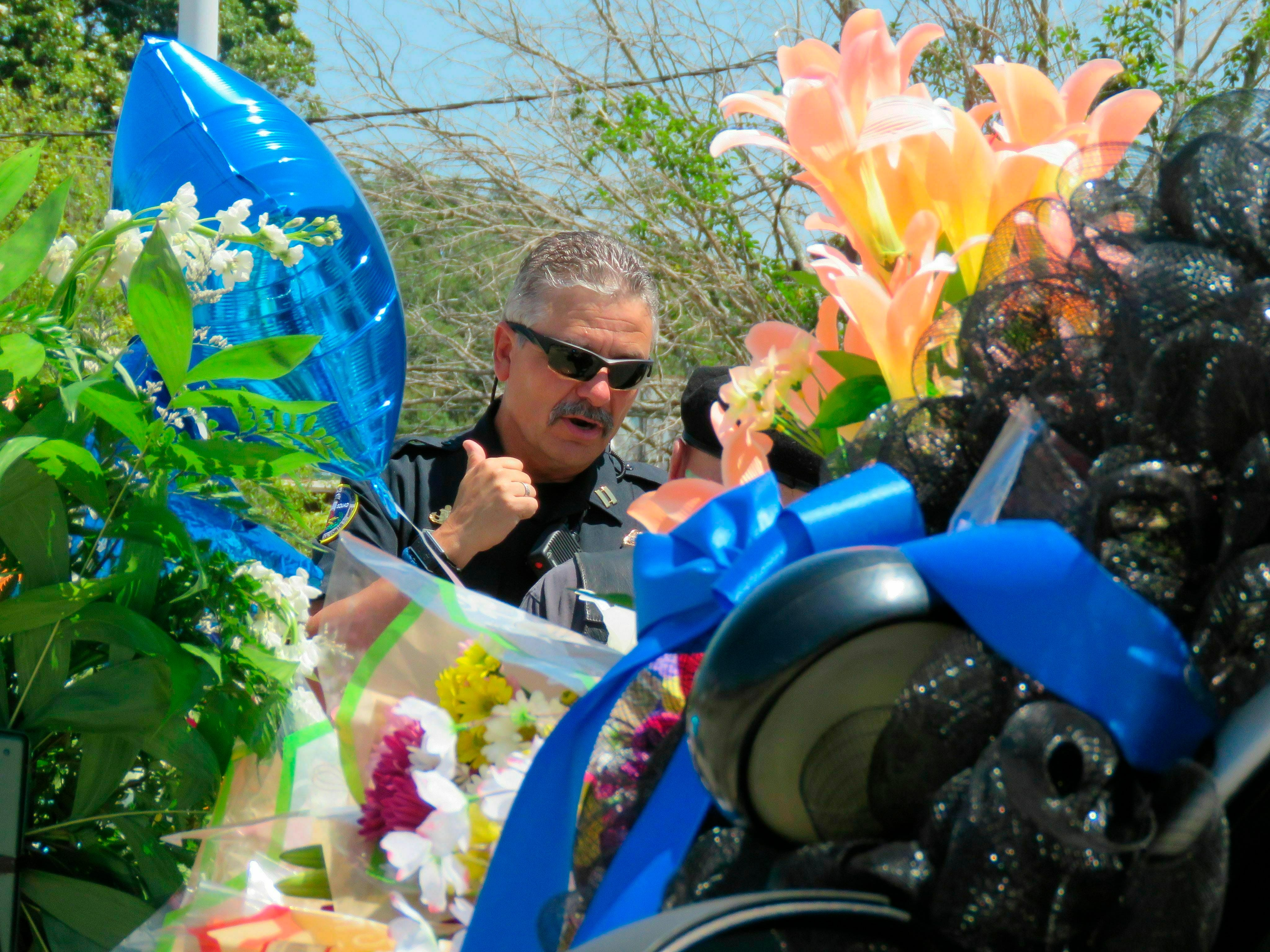 A Biloxi police vehicle that was assigned to patrolman Robert McKeithen is covered in flowers as Biloxi Police Capt. Milton Houseman, rear, talks , with a member of the Combat Veterans Motorcycle Association, Tuesday, May 7, 2019, in Biloxi, Miss. Houseman said he was one of the officers who brought Darian Tawan Atkinson, 19, to Biloxi after his arrest in Wiggins on May 6, in the death of Patrolman McKeithen.