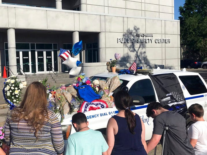 Citizens join hands and offer prayer Monday afternoon, May 6, 2019, at the Biloxi, Miss., Police Department, around the official SUV of Officer Robert McKeithen, who was murdered outside the building Sunday night. Area residents decorated the vehicle with memorials, flowers, and messages throughout the day.