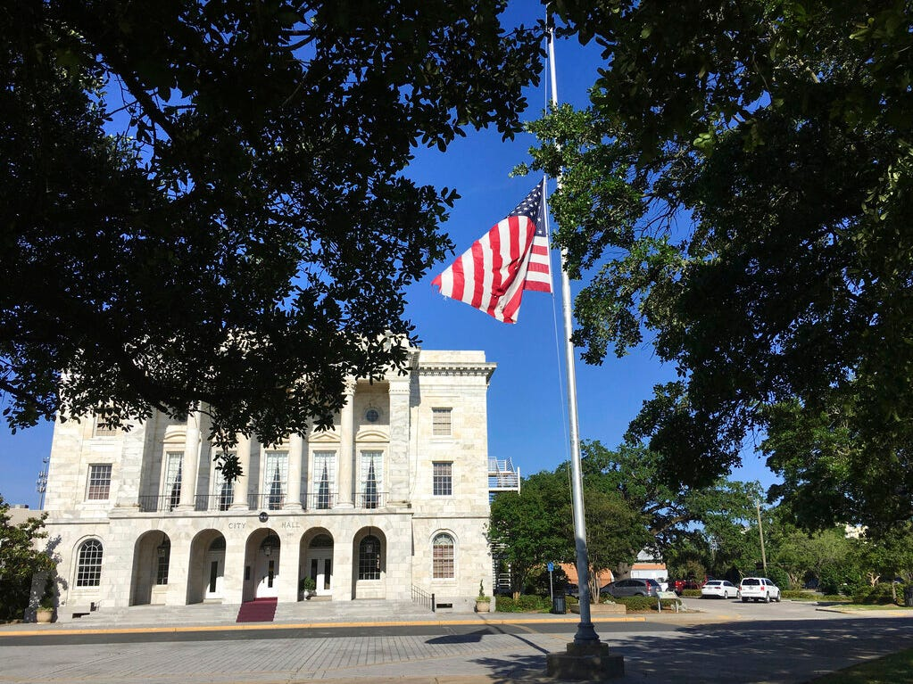 In this photo provided by WLOX, a flag flies at half-staff in front of the Biloxi, Miss., City Hall on Monday, May, 6, 2019, in memory of Biloxi Police Officer Robert McKeithen, who was shot in an ambush in front of the police station Sunday night.
