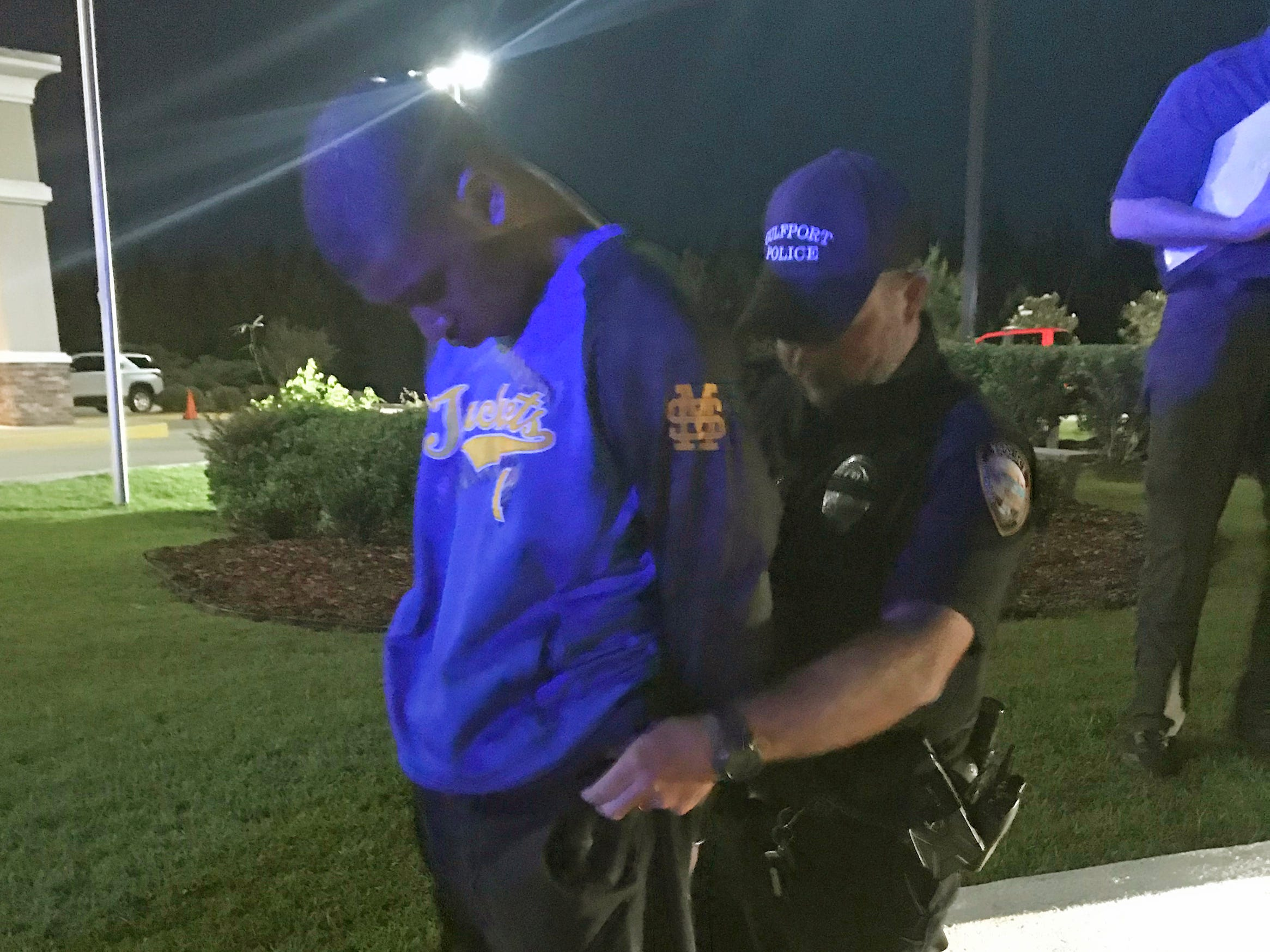 In this Monday, May 6, 2019 photo provided by the Stone County Enterprise newspaper, a Gulfport, Miss., police officer checks the pockets of Darian Tawan Atkinson, wanted for capital murder in the slaying of Biloxi Patrolman Robert McKeithen, as he is apprehended in Wiggins, Miss.