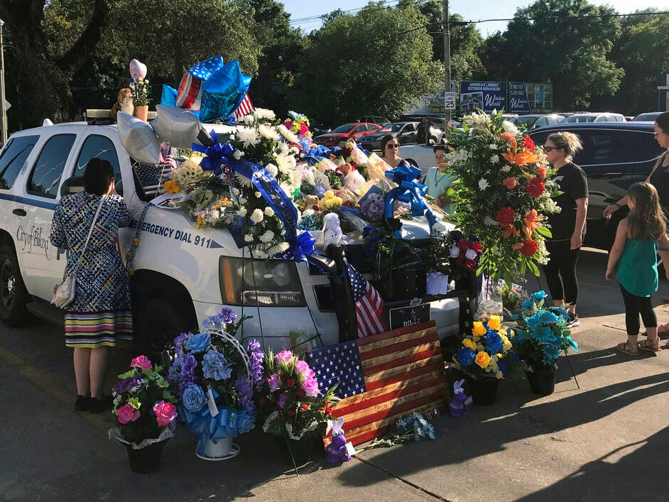 The police SUV of police Officer Robert McKeithen is decorated with memorials, flowers, and messages outside the Biloxi Police Department in Biloxi, Miss., Monday, May 6, 2019, a day after the officer was killed outside the building.