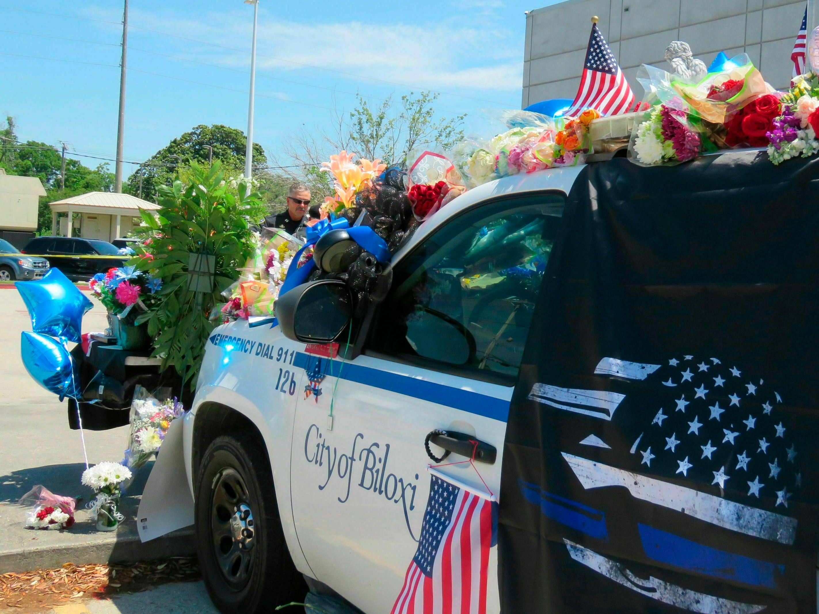 A Biloxi police vehicle that was assigned to patrolman Robert McKeithen is covered in flowers as Biloxi Police Capt. Milton Houseman, rear, talks , with a member of the Combat Veterans Motorcycle Association, Tuesday, May 7, 2019, in Biloxi, Miss.