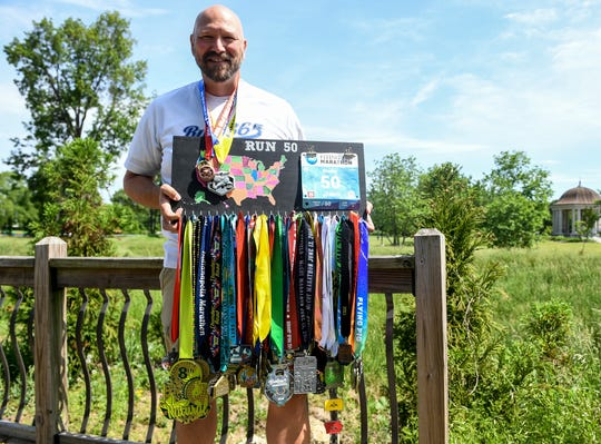 Jackson native Scott Stader shows off medals he has received from completing marathons in all 50 states.