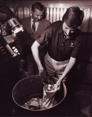 Assistant U.S. Attorney Guy Blackwell with one of several barrels of coins recovered in April 1987 from  bankrupt financier C.H. Butcher Jr., who had concealed many assets following the 1983 failure of his bank.