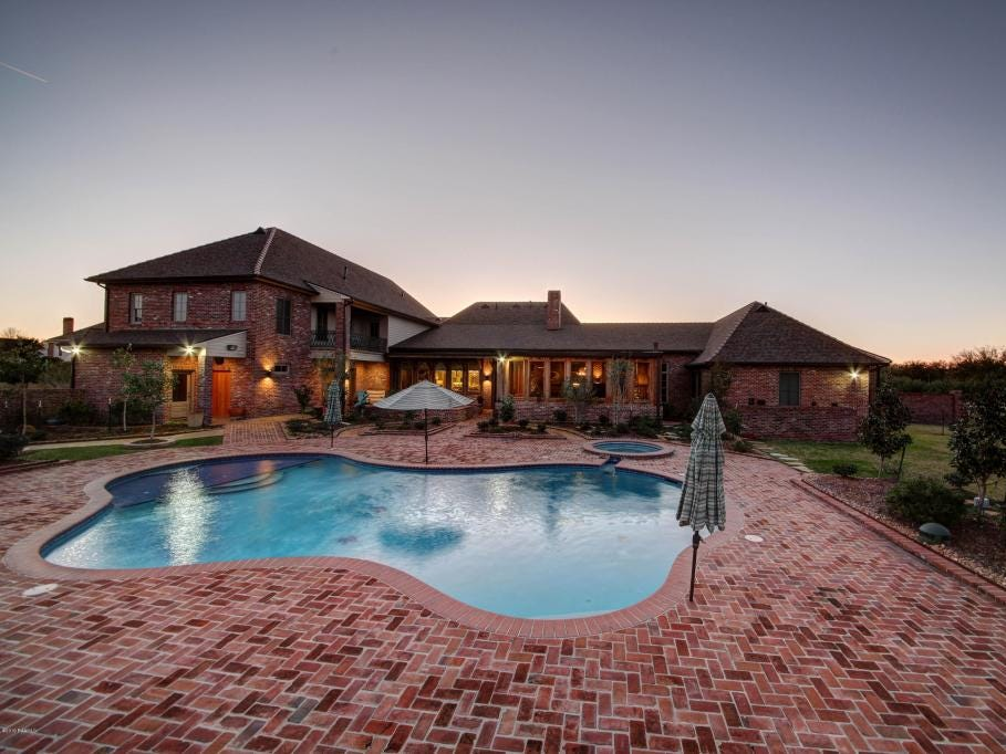 The backyard of the nearly 8,000-square-foot Youngsville mansion includes a pool, hot tub, screened porch, fire pit and much more.