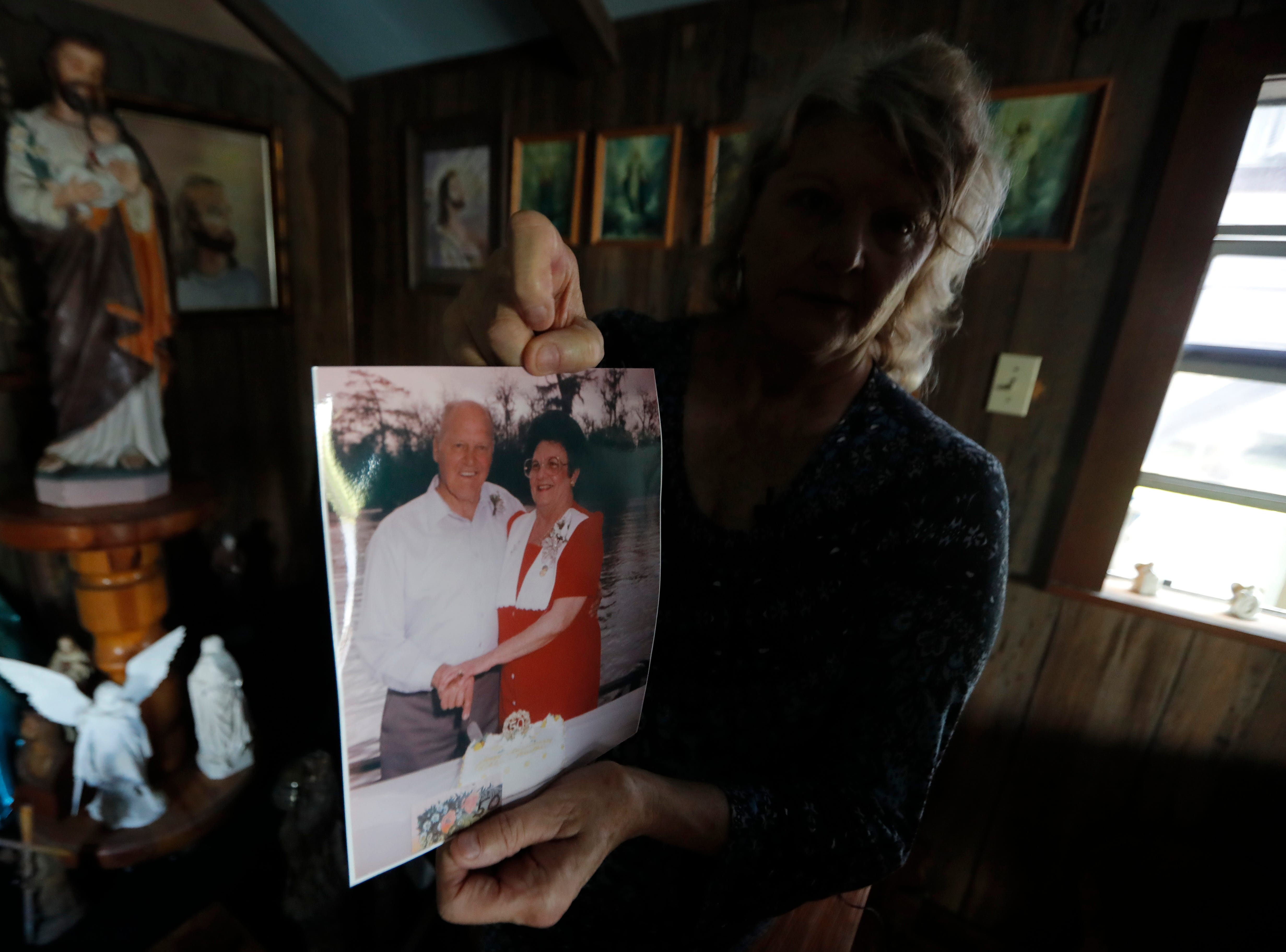 Pat Hymel shows a photo of her parents Martha and Bobby Deroche, inside Our Lady of Blind River Chapel, along the Blind River in St. James Parish, La., Tuesday, April 9, 2019. The chapel was built decades ago by her parents, after Martha had a vision of Jesus kneeling by a rock. Over the years, people have stopped by in boats or kayaks to pray in the one-room chapel. But floods over the years have damaged the little church, and the couple's grandson Lance Weber had to close it about two years ago out of safety concerns. (AP Photo/Gerald Herbert)