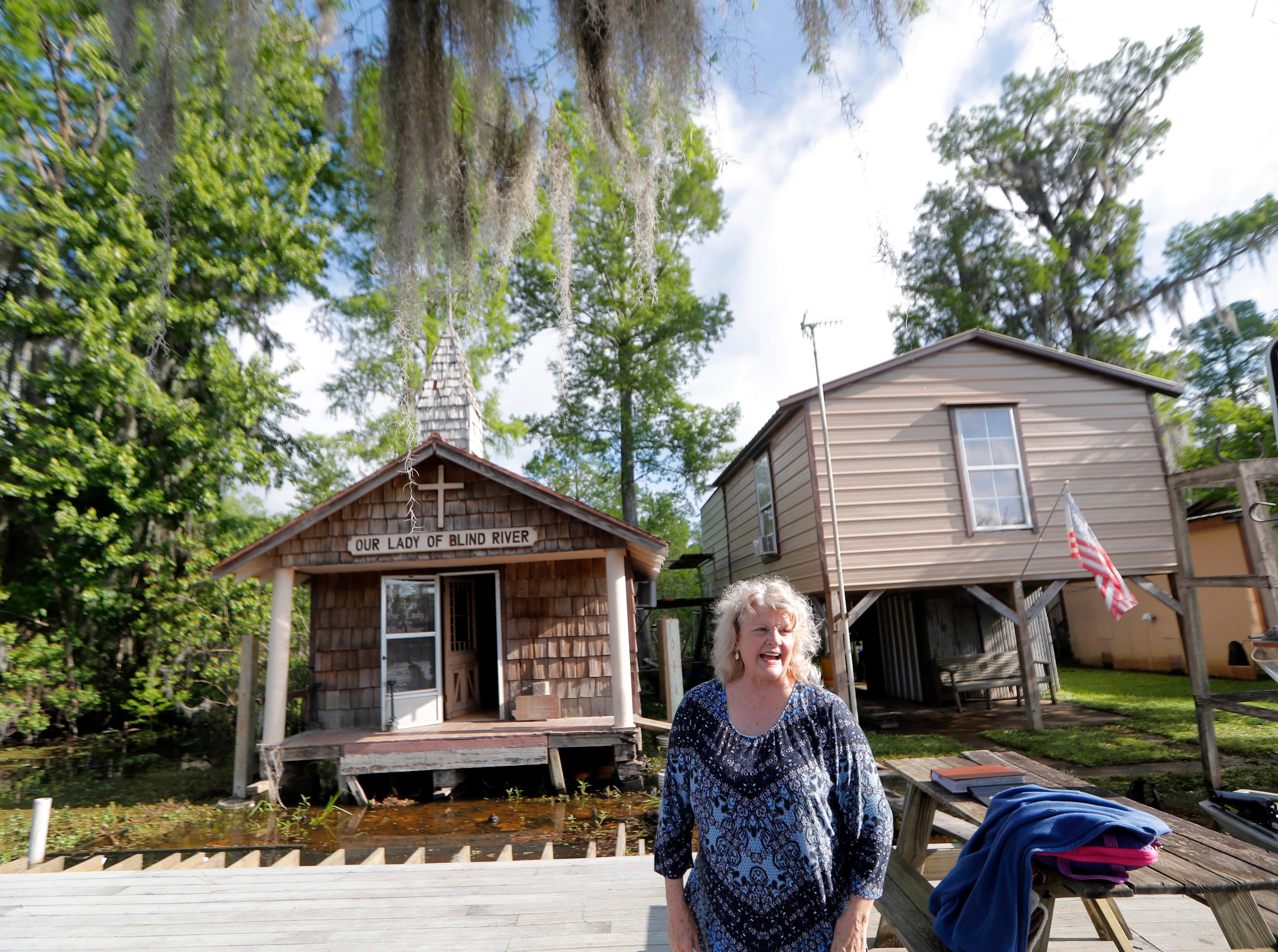 Pat Hymel stands on the dock in front of Our Lady of Blind River Chapel, along Blind River in St. James Parish, La., Tuesday, April 9, 2019. The chapel was built decades ago by her parents, Martha Deroche and her husband Bobby, after Martha had a vision of Jesus kneeling by a rock. Over the years, people have stopped by in boats or kayaks to pray in the one-room chapel. But floods over the years have damaged the little church, and the couple's grandson Lance Weber had to close it about two years ago out of safety concerns. (AP Photo/Gerald Herbert)