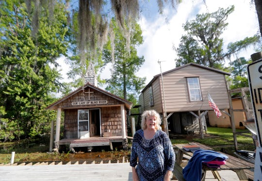 Pat Hymel stands on the dock in front of Our Lady of Blind River Chapel in St. James Parish, La. The chapel was built decades ago by her parents, Martha and Bobby Deroche.