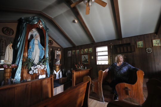 Pat Hymel sits inside of Our Lady of Blind River Chapel, along the Blind River in St. James Parish, La., Tuesday, April 9, 2019. The chapel was built decades ago by her parents, Martha Deroche and her husband, Bobby, after Martha had a vision of Jesus kneeling by a rock. Over the years, people have stopped by in boats or kayaks to pray in the one-room chapel. But floods over the years have damaged the little church, and the couple's grandson Lance Weber had to close it about two years ago out of safety concerns.(AP Photo/Gerald Herbert)