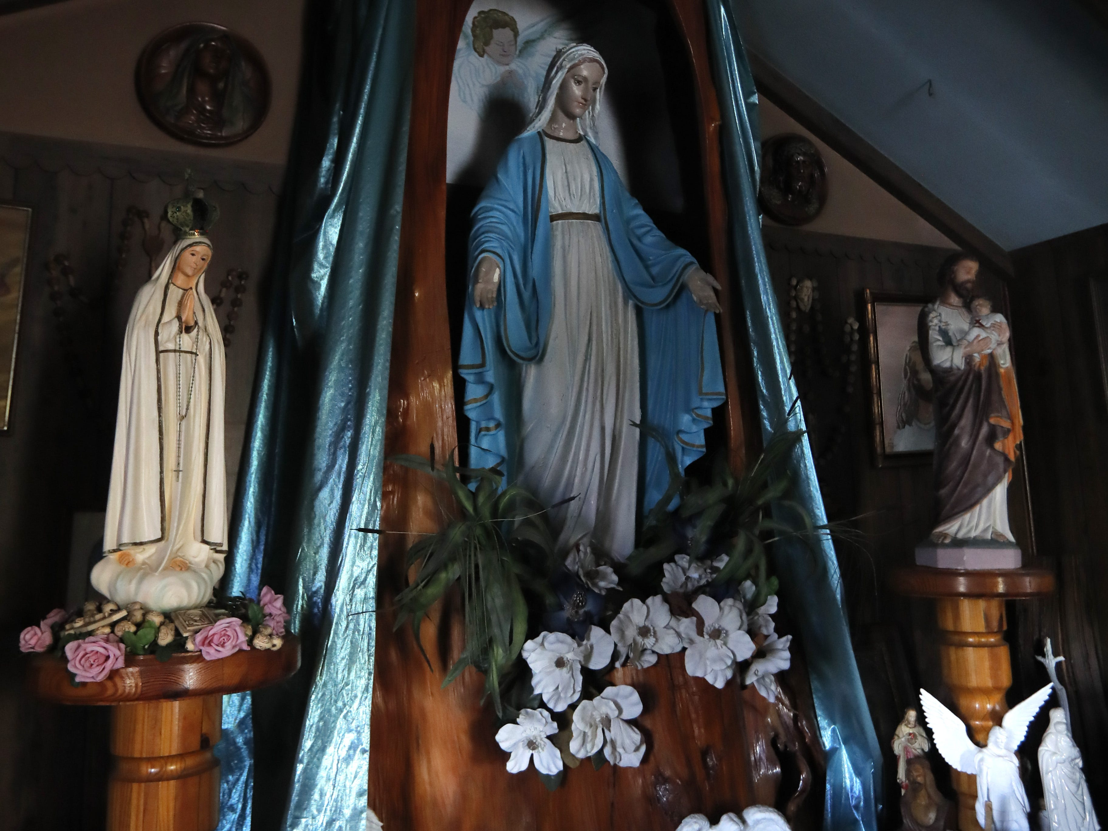A statue of the Virgin Mary sits inside a carved cypress stump inside Our Lady of Blind River Chapel in St. James Parish, La., Tuesday, April 9, 2019. The chapel was built decades ago by Martha Deroche and her husband Bobby, after Martha had a vision of Jesus kneeling by a rock. Over the years, people have stopped by in boats or kayaks to pray in the one-room chapel. But floods over the years have damaged the little church, and the couple's grandson Lance Weber had to close it about two years ago out of safety concerns. (AP Photo/Gerald Herbert)
