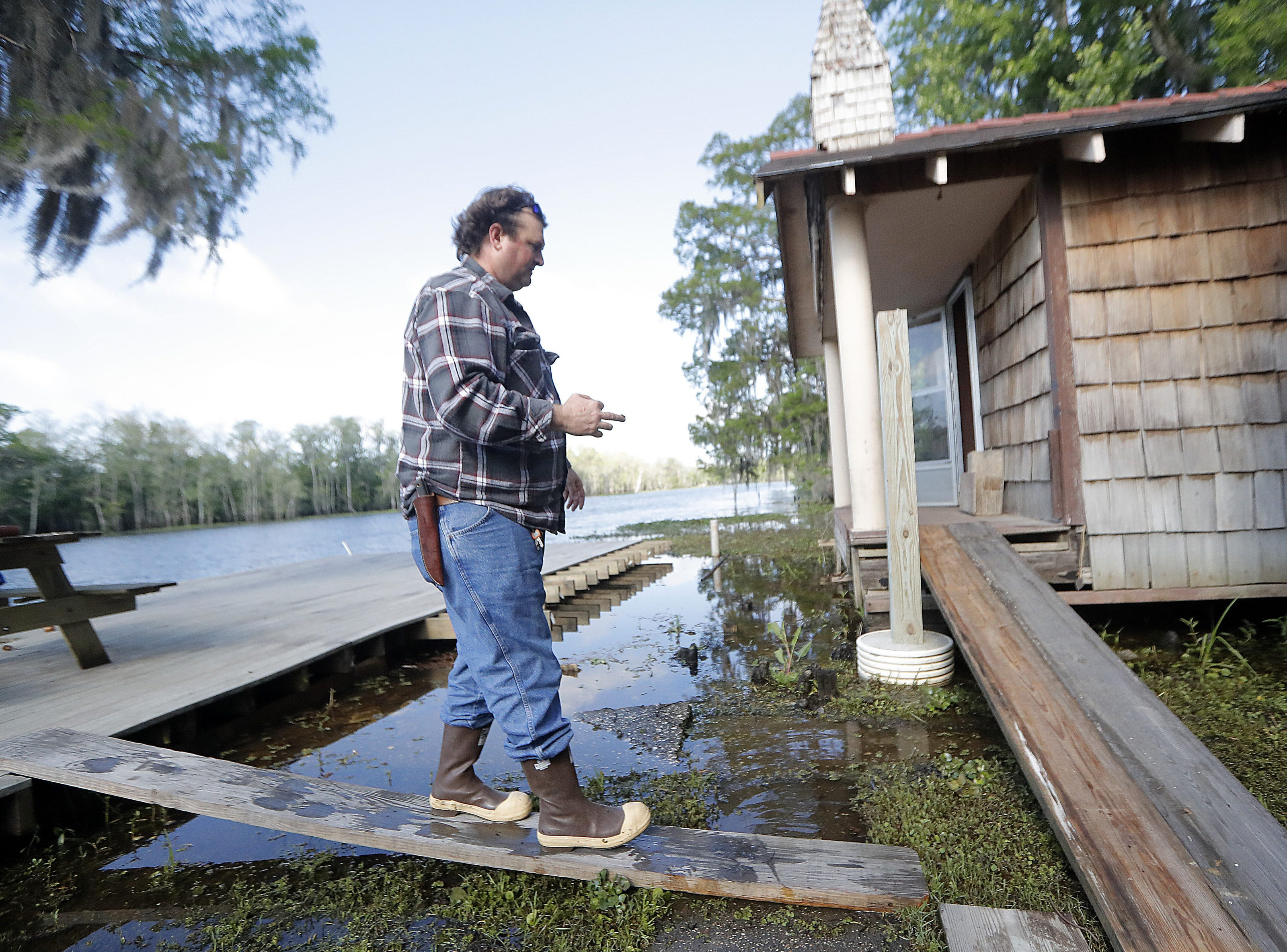 Lance Weber walks on a plank on the dock outside Our Lady of Blind River Chapel in St. James Parish, La., Tuesday, April 9, 2019. The chapel was built decades ago by his grandparents, Martha Deroche and her husband Bobby, after Martha had a vision of Jesus kneeling by a rock. Over the years, people have stopped by in boats or kayaks to pray in the one-room chapel. But floods over the years have damaged the little church, and Lance had to close it about two years ago out of safety concerns. (AP Photo/Gerald Herbert)