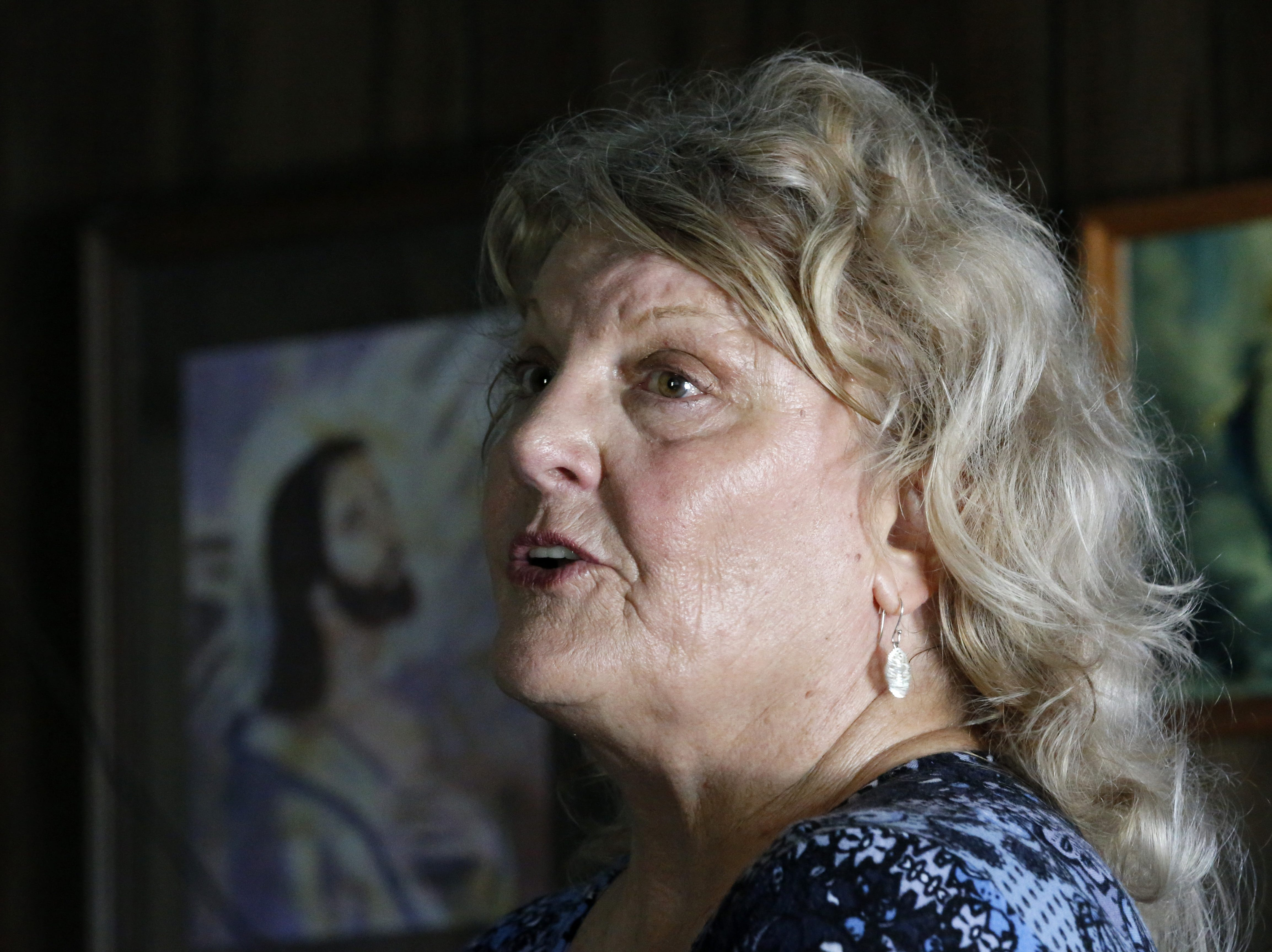 Pat Hymel tells the history of Our Lady of Blind River Chapel, inside the chapel along Blind River in St. James Parish, La., Tuesday, April 9, 2019. The chapel was built decades ago by Martha Deroche and her husband, Bobby, after Martha had a vision of Jesus kneeling by a rock. Over the years, people have stopped by in boats or kayaks to pray in the one-room chapel. But floods over the years have damaged the little church, and the couple's grandson Lance Weber had to close it about two years ago out of safety concerns. (AP Photo/Gerald Herbert)
