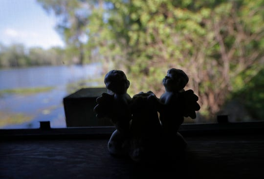 Angel figurines sit on a windowsill inside Our Lady of Blind River Chapel, along Blind River, in St. James Parish, La., Tuesday, April 9, 2019. The chapel was built decades ago by Martha Deroche and her husband Bobby, after Martha had a vision of Jesus kneeling by a rock. Over the years, people have stopped by in boats or kayaks to pray in the one-room chapel. But floods over the years have damaged the little church, and the couple's grandson Lance Weber had to close it about two years ago out of safety concerns. (AP Photo/Gerald Herbert)