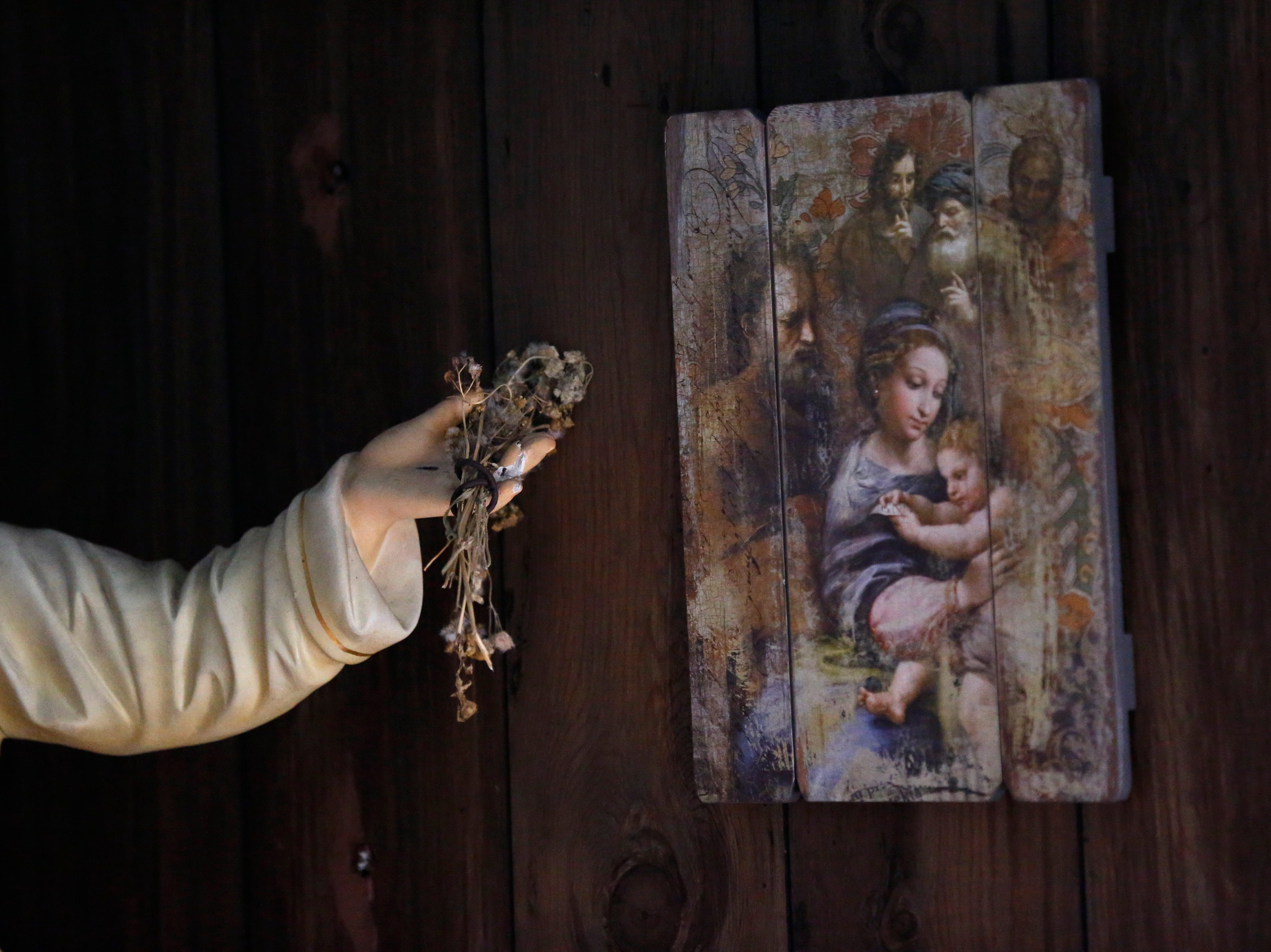 A statue of Jesus has dried flowers placed in its hand, with religious art adorning the walls, inside Our Lady of Blind River Chapel, along Blind River, in St. James Parish, La., Tuesday, April 9, 2019. The chapel was built decades ago by Martha Deroche and her husband, Bobby, after Martha had a vision of Jesus kneeling by a rock. Over the years, people have stopped by in boats or kayaks to pray in the one-room chapel. But floods over the years have damaged the little church, and the couple's grandson Lance Weber had to close it about two years ago out of safety concerns. (AP Photo/Gerald Herbert)