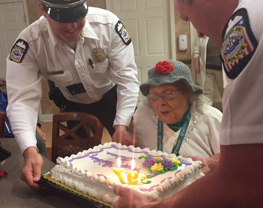 Columbus Police Department Officers Adam Hardwick and Mel Romans help Carroll Place resident Thelma Ayler celebrate her 97th birthday Monday.