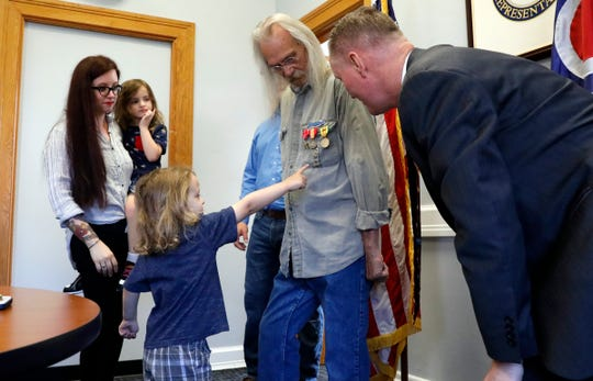 Malachi Draper, 3, points to his grandfather Tom Crissinger's Expert Pistol and Rifle badge after U.S. Rep. Steve Stivers asked Malachi which one he liked best Tuesday morning, May 7, 2019, in Lancaster. Stivers presented Crissinger with seven medals the Lancaster resident and Vietnam Veteran earned during his three years of services in Vietnam with the U.S. Army. Among the awards was a Bronze Star medal with a valor device.