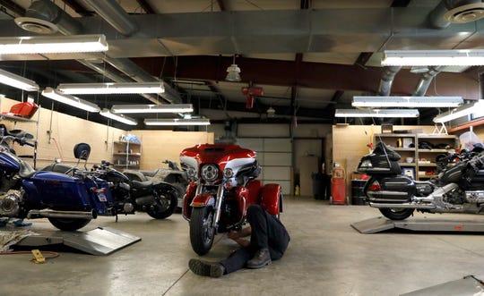 A technician works in the garage at Joe Carson Honda and Harley-Davidson Tuesday morning, May 7, 2019, in Carroll.