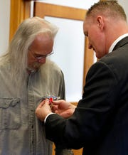 U.S. Rep. Steve Stivers pins medals Tom Crissinger earned during the Vietnam War onto his shirt Tuesday morning, May 7, 2019, in Stivers' field office in Lancaster. Crissinger was awarded seven medals including a Bronze Star medal with a valor device.