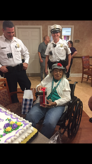 Columbus Police Department Officers Adam Hardwick and Amber Rich watch as Carroll Place resident Thelma Ayler opens presents the police department got her on her 97th birthday Monday.
