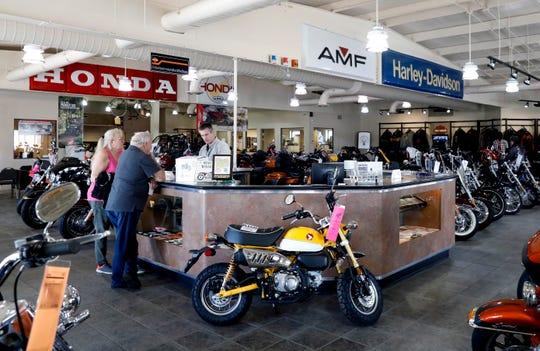 Customers talk to an employee at Joe Carson Honda and Harley-Davidson Tuesday, May 7, 2019, in Lancaster.