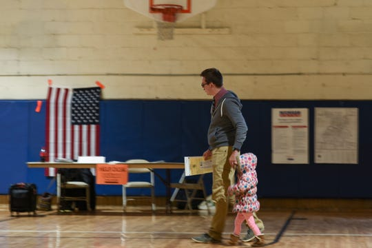 """Ballot in one hand and two-year-old daughter Frida in the other, John Schneider of Lansing prepares to cast his vote Tuesday, May 7, 2019, at the Foster Community Center on the eastside. """"Education is important, and our kids will be going to the Lansing School District,"""" Schneider remarked, as he voted on a millage proposal for the Lansing School District."""