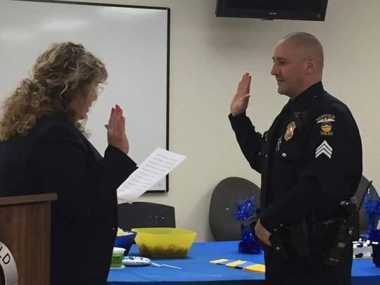 Mansfield Safety-Services Director Lori Cope swears in Lt. Don Rhinehart in a ceremony Tuesday.