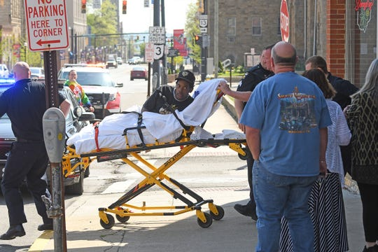 A shooting victim, identified by police as Brian Webber, 41, is wheeled on a gurney to an ambulance after being shot near West Second Street on Tuesday morning.