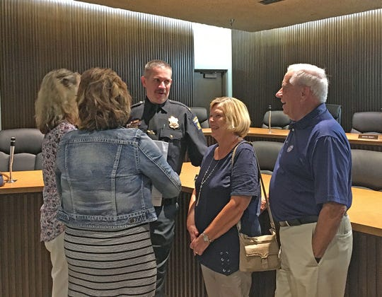 Joe Petrycki was sworn in as Mansfield assistant police chief Tuesday. His parents at right, Marilyn and Nick Petrycki, along with his wife Amy, far left, congratulate him at Mansfield City Council Chambers.