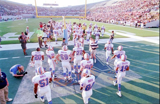 The Tennessee Oilers walk across the University of Memphis logo as they take the field in a preseason game against the New Orleans Saints at Liberty Bowl Memorial Stadium in Memphis on Aug. 2, 1997.