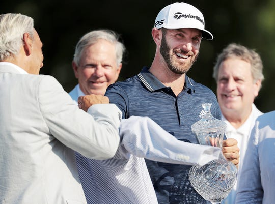 Dustin Johnson receives his seersucker jacket and trophy after holing out on the 18th hole to win the  FedEx St. Jude Classic Golf Tournament at Southwind in Memphis in June 2018.