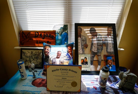 A shrine of Dejuan Hill at his mother's Uptown home includes photos, a blanket with his face on it and his high school diploma.