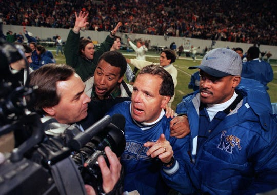 Former Memphis football coach Rip Scherer, center, talks with the media following the Tigers' first win over Tennessee in program history. The game was played at Liberty Bowl Memorial Stadium on Nov. 9, 1996.