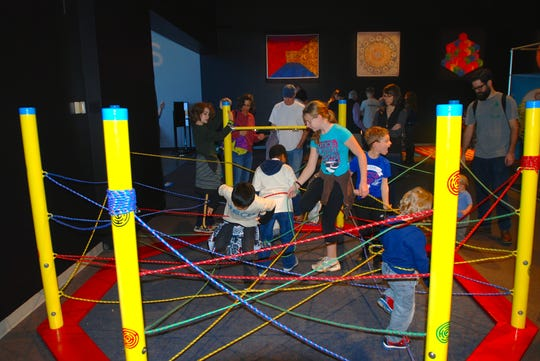 Kids have to maneuver their way under and over ropes in the web maze at the Mazes & Brain Games exhibit at Discovery World.