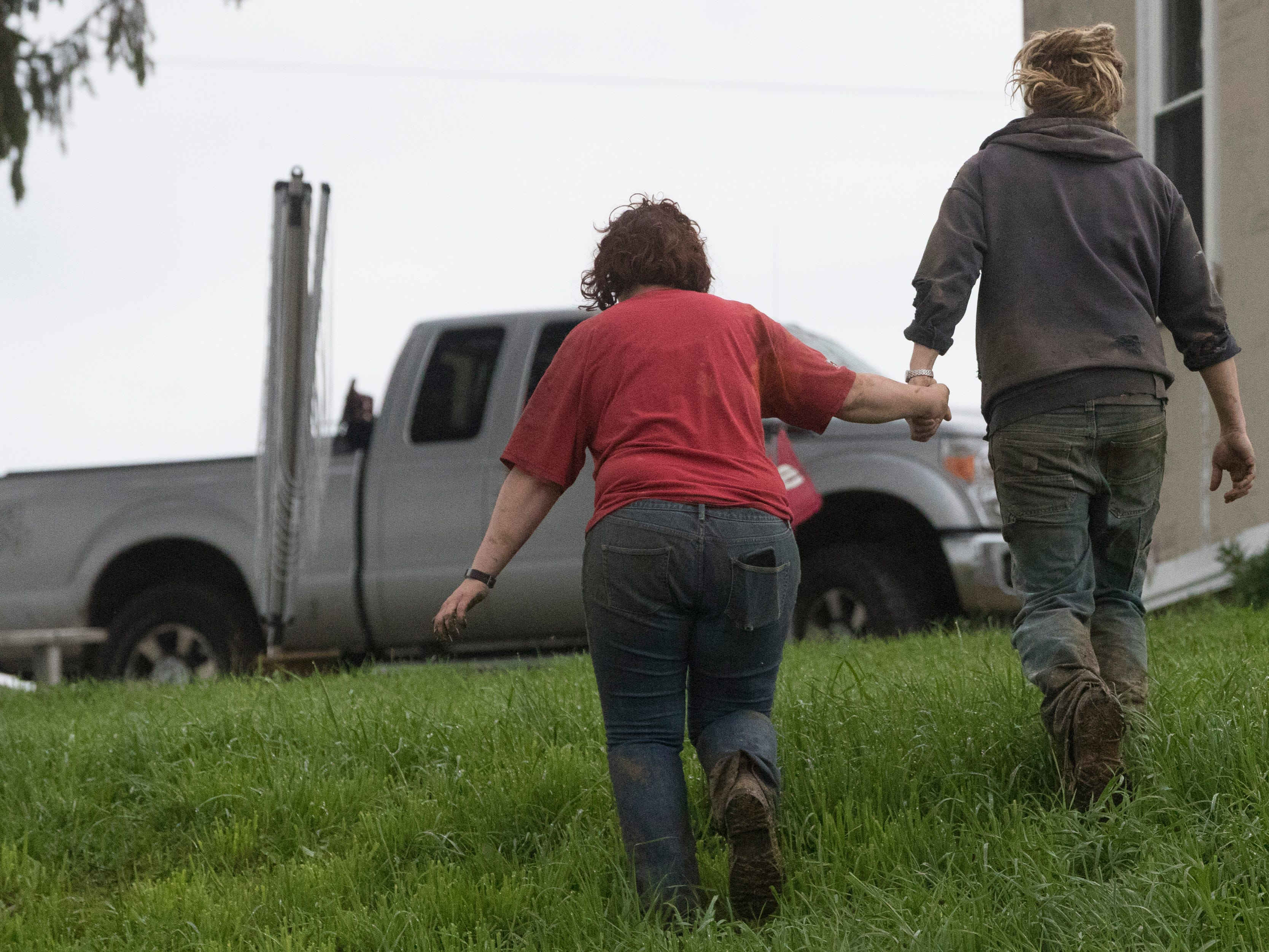 Brandi and Emily Harris walk to their truck to check on two cows that got loose while being loaded onto a truck.