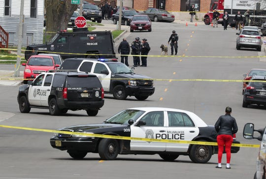 Investigators respond to the scene of an officer-involved shooting on West Windlake Avenue in which one of two people who approached plainclothes officers in what is believed to be a robbery attempt was shot and killed in Milwaukee on Tuesday.