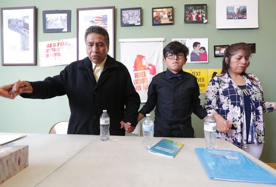 Raymundo Martinez-Moreno, left, his grandson, Sergio Martinez, 10, and his wife say a prayer before a news conference.