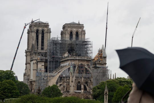 Cranes work at Notre Dame cathedral, in Paris, Thursday, April 25, 2019. French police scientists were starting to examine Notre Dame Cathedral on Thursday for the first time since last week's devastating fire. (AP Photo/Thibault Camus)