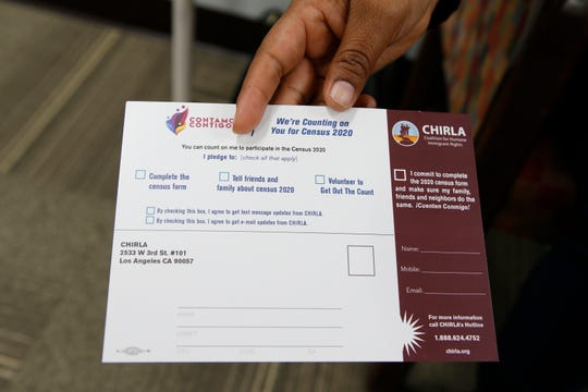 """In this Friday, April 26, 2019, photo, Coalition for Humane Immigrant Rights, CHIRLA volunteer Angeles Rosales holds up a CHIRLA """"Contamos Contigo,"""" """"We Count with You"""" census campaign card at the CHIRLA offices in Los Angeles. It's not just Democratic-leaning states at risk of losing federal money and clout in Congress if the Supreme Court says the upcoming census can include a citizenship question. Fast-growing Arizona, Florida and Texas all have large groups of immigrants, especially Hispanics, who might choose to sit out the census, but are led by Republicans who seem unconcerned about the potential for an undercount and the resulting loss of representation in Congress. (AP Photo/Damian Dovarganes)"""