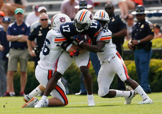 Auburn wide receiver Marquis McClain (17 blue) is tackled by defensive defensive backs Roger McCreary (17 white) and Richard Jubnor (37) during the A-Day game at Jordan-Hare Stadium on April 13, 2019.