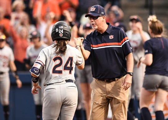 Auburn coach Mickey Dean (right) congratulates Kendall Veach (24) after a home run against South Carolina on Friday, April 12, 2019, in Auburn, Ala.