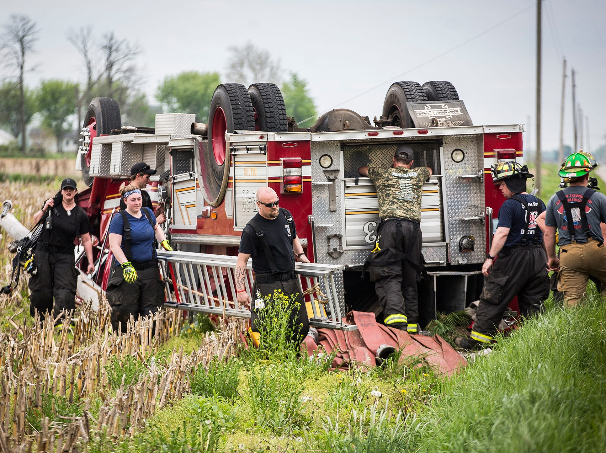 State and county police as well as other firefighters respond at the scene of a rollover wreck involving a Salem Township firetruck on S. 300 W. near the Henry County line at around 3:45 p.m. Saturday. According to police, the firetruck was in the vicinity of the scene of a field fire which other firefighters had quelled at the time the accident occurred. Two firefighters were trapped inside the rolled vehicle by live electrical wires which had become entangled with the truck. The trapped firefighters were extricated and transported to the hospital with non-life threatening injuries. The incident is being investigated.