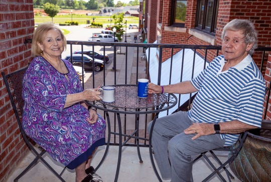 Rosa and Alberto Garcia make use of their balcony outside their home in Pleasant View Village overlooking the shops, restaurants and green space of their community Monday, May 6, 2019.